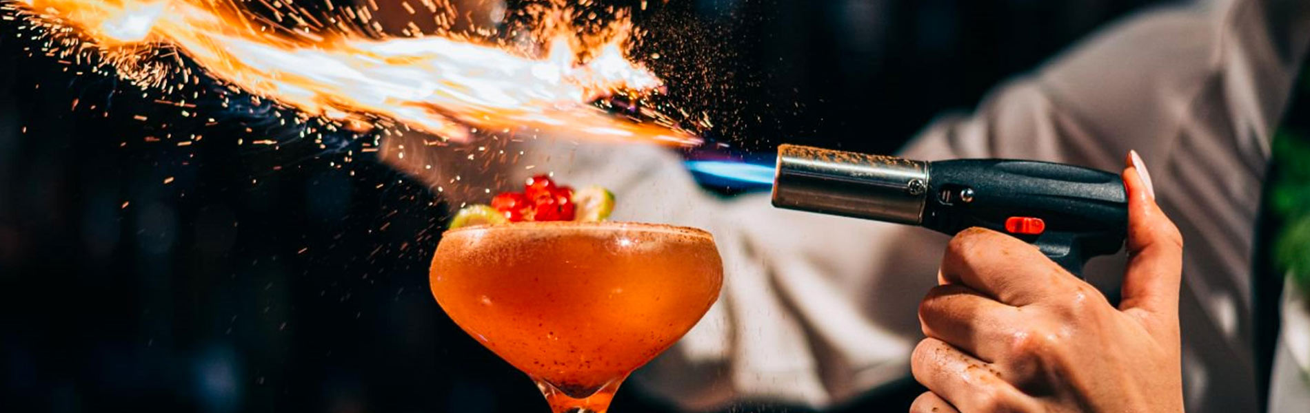 Bartender with a torch lighting a cocktail on fire